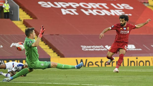 Liverpool's Mohamed Salah scores his side's second goal during the English Premier League soccer match between Liverpool and Crystal Palace at Anfield Stadium in Liverpool, England, Wednesday, June 24, 2020. (Shaun Botterill/Pool via AP)