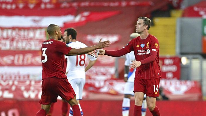 Liverpools Jordan Henderson, right, hands the captains armband to Liverpools Fabinho as he is substituted during the English Premier League soccer match between Liverpool and Crystal Palace at Anfield Stadium in Liverpool, England, Wednesday, June 24, 2020. (Paul Ellis/Pool via AP)