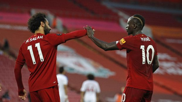 Liverpool's Sadio Mane, right, celebrates scoring his side's fourth goal with Mo Salah during the English Premier League soccer match between Liverpool and Crystal Palace at Anfield Stadium in Liverpool, England, Wednesday, June 24, 2020. (Phil Noble/Pool via AP)