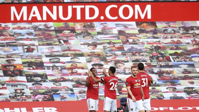 Manchester Uniteds Anthony Martial, left, celebrates with his teammates, after scoring his sides third goal during the English Premier League soccer match between Manchester United and Sheffield United at Old Trafford in Manchester, England, Wednesday, June 24, 2020. (Michael Regan/Pool via AP)