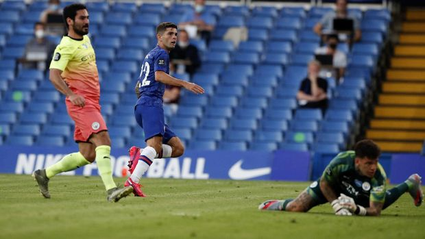Chelsea's Christian Pulisic, centre, watches the ball as he scores his teams first goal during the English Premier League soccer match between Chelsea and Manchester City at Stamford Bridge, in London, England, Thursday, June 25, 2020. (AP Photo/Paul Childs,Pool)