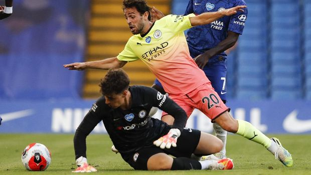 Manchester City's Bernardo Silva, right, attempts to kick the ball past Chelsea's goalkeeper Kepa Arrizabalaga during the English Premier League soccer match between Chelsea and Manchester City at Stamford Bridge, in London, England, Thursday, June 25, 2020. (AP Photo/Adrian Dennis,Pool)