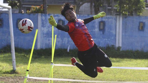 Penjaga gawang tim Arema FC, Kartika Aji berusaha menepis bola saat mengikuti latihan di lapangan Satsui Tubun, Malang, Jawa Timur, Kamis (25/6/2020). Latihan yang dilakukan di masa transisi normal baru tersebut hanya diikuti para pesepakbola yang berposisi sebagai penjaga gawang sementara pemain lainnya mengikuti latihan secara daring dari rumah. ANTARA FOTO/Ari Bowo Sucipto/aww.