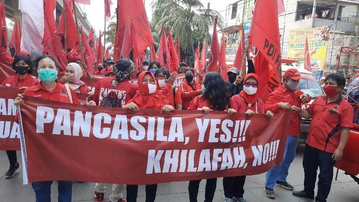 Massa DPC PDIP Jakut bentangkan spanduk di Jalan Yos Sudarso, Jakarta Utara, Jumat (26/6/2020).