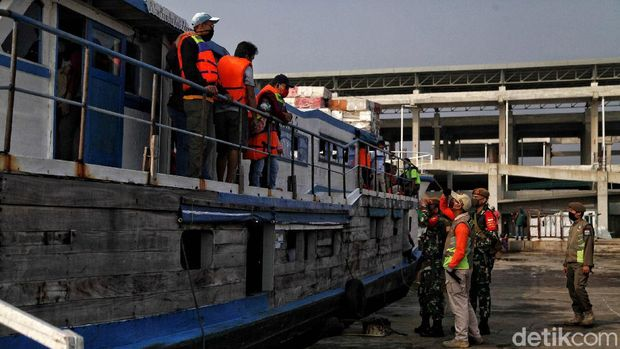 Officers check the temperature of passengers on the KMP Arwana ship destined for Pramuka Island in the Kali Adem Port area, Muara Angke, North Jakarta, Friday (26/6).  Currently, Kali Adem Muara Angke port, which serves trips to the Thousand Islands and the reverse direction, has reopened.