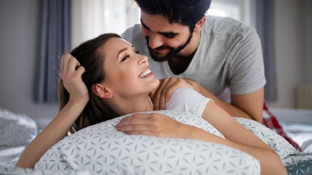 Cheerful young happy couple making massage at home