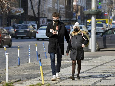 Kyiv, Ukraine - March 18, 2020: Pregnant woman and man with plaster on hand in protective medical mask walking down the street. Due to the coronavirus epidemic, the Ukrainian government has closed the subway.