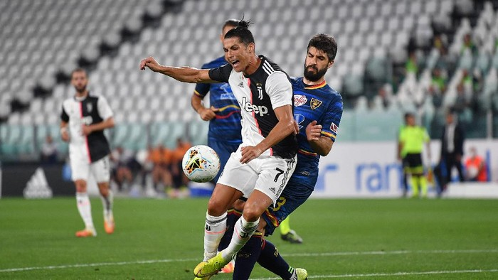 TURIN, ITALY - JUNE 26:  Cristiano Ronaldo of Juventus is tackled by Luca Rossettini of US Lecce during the Serie A match between Juventus and  US Lecce at Allianz Stadium on June 26, 2020 in Turin, Italy.  (Photo by Valerio Pennicino/Getty Images)