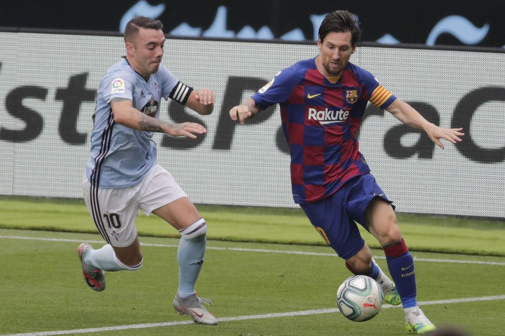 Barcelona's Lionel Messi, right, fights for the ball with Celta Vigo's Iago Aspas during a Spanish La Liga soccer match between RC Celta and Barcelona at the Balaidos stadium in Vigo, Spain, Saturday, June 27, 2020. (AP Photo/Lalo Villar)