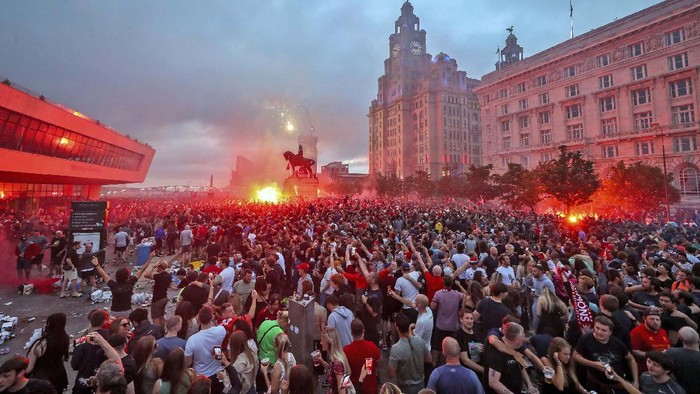 A workman clears up rubbish outside the Liver building in Liverpool after fans celebrated in the city last night following Liverpool FC winning the Premier League on Thursday night, Saturday June 27, 2020. (Peter Byrne/PA via AP)