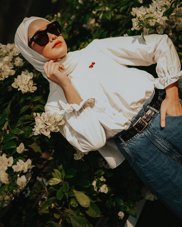 Ana memilih gaya fashion kasual dengan mengenakan kemeja putih dan bawahan celana jeans, lalu hijab putih.