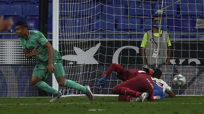Real Madrids Casemiro, left, celebrates after scoring the opening goal during the Spanish La Liga soccer match between RCD Espanyol and Real Madrid at the Cornella-El Prat stadium in Barcelona, Spain, Sunday, June 28, 2020. (AP Photo/Joan Monfort)