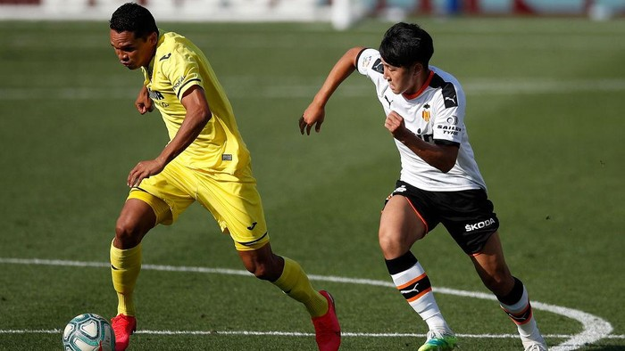 VILLAREAL, SPAIN - JUNE 28: Carlos Bacca (l) of Villareal is tracked by Lee Kang-In of Valencia during the Liga match between Villarreal CF and Valencia CF at Estadio de la Ceramica on June 28, 2020 in Villareal, Spain. (Photo by Eric Alonso/Getty Images)