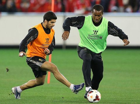 MELBOURNE, AUSTRALIA - JULY 23:  Luis Suarez (L) and Andre Wisdom contest for the ball during a Liverpool FC training session at Melbourne Cricket Ground on July 23, 2013 in Melbourne, Australia.  (Photo by Michael Dodge/Getty Images)