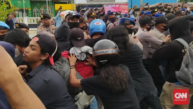 Mahasiswa dan polisi terlibat saling dorong dalam demo tolak kedatangan TKA China di pintu masuk Bandara Haluoleo Kendari. (CNNIndonesia/Fandi)