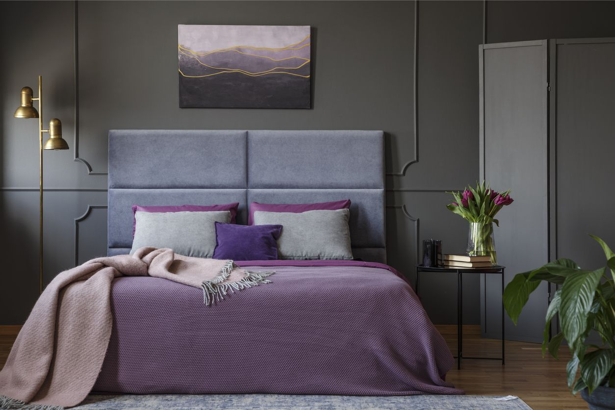 Pastel blanket on pink bed in woman's bedroom interior with gold lamp and poster