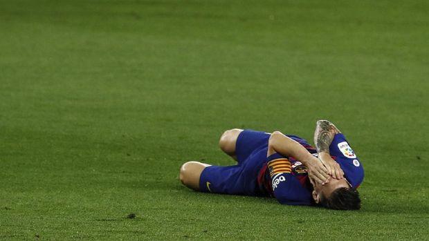 Barcelona's Lionel Messi grimaces in pain during the Spanish La Liga soccer match between RCD Espanyol and Real Madrid at the Cornella-El Prat stadium in Barcelona, Spain, Sunday, June 28, 2020. (AP Photo/Joan Monfort)