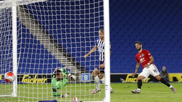 Manchester United's Bruno Fernandes, right, scores his side's third goal during the English Premier League soccer match between Brighton & Hove Albion and Manchester United at the AMEX Stadium in Brighton, England, Tuesday, June 30, 2020. (AP Photo/Alastair Grant, Pool)