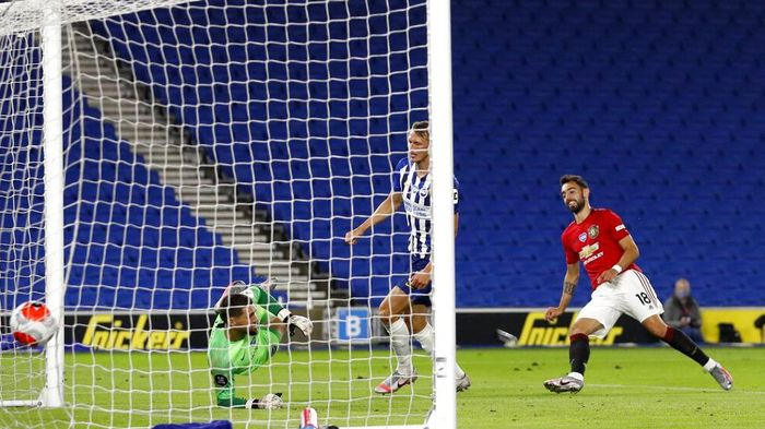 Manchester Uniteds Bruno Fernandes, right, scores his sides third goal during the English Premier League soccer match between Brighton & Hove Albion and Manchester United at the AMEX Stadium in Brighton, England, Tuesday, June 30, 2020. (AP Photo/Alastair Grant, Pool)