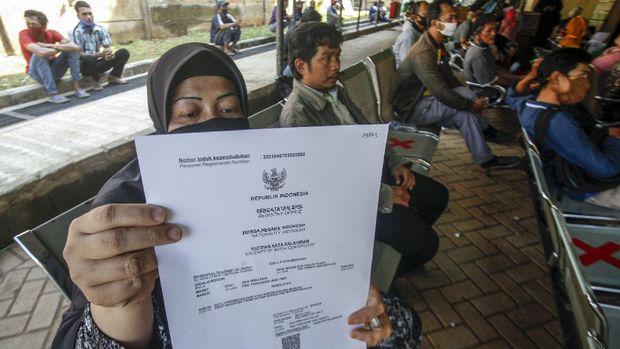 Warga menunjukan akta kelahiran yang dicetak menggunakan media kertas HVS di Kantor Disdukcapil, Kabupaten Bogor, Jawa Barat, Rabu (1/7/2020). Kemendagri kembali mengeluarkan aturan baru dengan mengganti bahan pencetakan jenis akta kelahiran hingga Kartu Keluarga (KK) menggunakan media kertas HVS A4 80 gram. ANTARA FOTO/Yulius Satria Wijaya/aww.