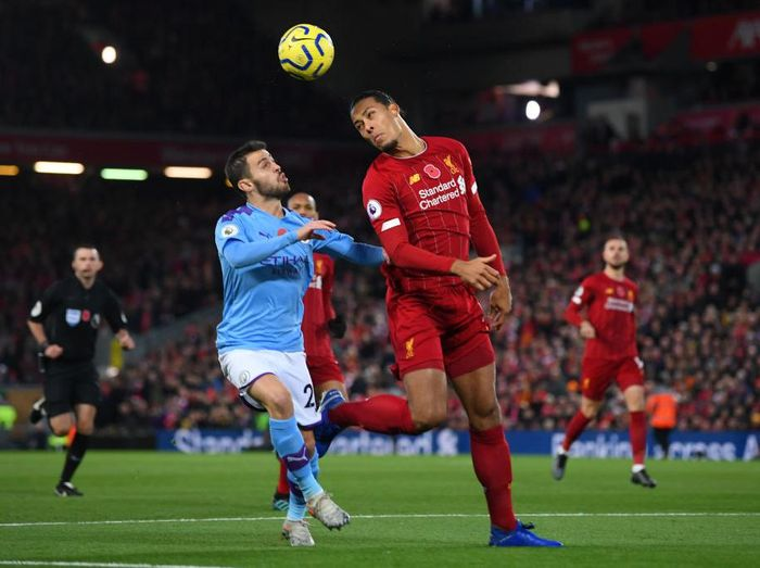 LIVERPOOL, ENGLAND - NOVEMBER 10: Virgil van Dijk of Liverpool heads the ball clear as he is put under pressure by Bernardo Silva of Manchester City during the Premier League match between Liverpool FC and Manchester City at Anfield on November 10, 2019 in Liverpool, United Kingdom. (Photo by Laurence Griffiths/Getty Images)