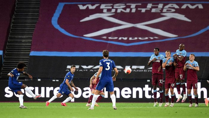 LONDON, ENGLAND - JULY 01: Willian of Chelsea scores his teams second goal from a free kick during the Premier League match between West Ham United and Chelsea FC at London Stadium on July 01, 2020 in London, England. Football Stadiums around Europe remain empty due to the Coronavirus Pandemic as Government social distancing laws prohibit fans inside venues resulting in all fixtures being played behind closed doors. (Photo by Michael Regan/Getty Images)