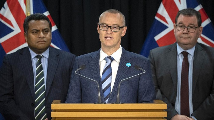 New Zealand Health Minister David Clark, center, flanked by Cabinet colleagues Grant Robertson, right, and Kris Faafoi addresses a press conference where he announced his resignation at parliament in Wellington, New Zealand Thursday, July 2, 2020. Clark resigned Thursday following a series of personal blunders during the coronavirus pandemic. (Mark Mitchell/New Zealand Herald via AP)