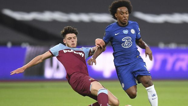 Chelsea's Willian, right is challenged for the ball by West Ham's Declan Rice during the English Premier League soccer match between West Ham United and Chelsea at the London Stadium stadium in London, Wednesday July 1, 2020. (Michael Regan/Pool via AP)