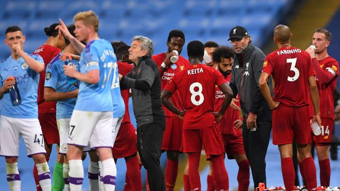 MANCHESTER, ENGLAND - JULY 02: Jurgen Klopp, Manager of Liverpool speaks to his players during a drinks break during the Premier League match between Manchester City and Liverpool FC at Etihad Stadium on July 02, 2020 in Manchester, England. Football Stadiums around Europe remain empty due to the Coronavirus Pandemic as Government social distancing laws prohibit fans inside venues resulting in all fixtures being played behind closed doors. (Photo by Laurence Griffiths/Getty Images)