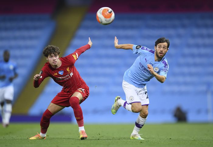 Manchester Citys Bernardo Silva, right, and Liverpools Neco Williams battle for the ball during the English Premier League soccer match between Manchester City and Liverpool at Etihad Stadium in Manchester, England, Thursday, July 2, 2020. (AP Photo/Laurence Griffiths,Pool)