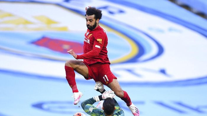 Liverpools Mohamed Salah leaps over Manchester Citys goalkeeper Ederson during the English Premier League soccer match between Manchester City and Liverpool at Etihad Stadium in Manchester, England, Thursday, July 2, 2020. (AP Photo/Laurence Griffiths,Pool)