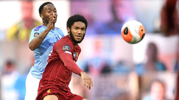Manchester City's Raheem Sterling, left, and Liverpool's Joe Gomez battle for the ball during the English Premier League soccer match between Manchester City and Liverpool at Etihad Stadium in Manchester, England, Thursday, July 2, 2020. (AP Photo/Peter Powell,Pool)