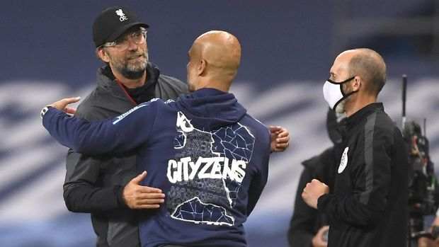 Liverpool's manager Jurgen Klopp, left, and Manchester City's head coach Pep Guardiola embrace after the English Premier League soccer match between Manchester City and Liverpool at Etihad Stadium in Manchester, England, Thursday, July 2, 2020. (AP Photo/Laurence Griffiths,Pool)