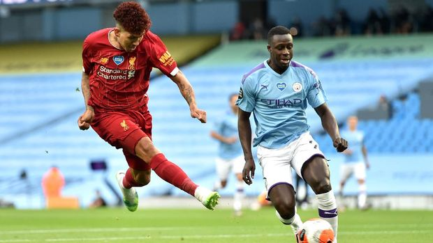 MANCHESTER, ENGLAND - JULY 02: Roberto Firmino of Liverpool shoots as he is challenged by Benjamin Mendy of Manchester City during the Premier League match between Manchester City and Liverpool FC at Etihad Stadium on July 02, 2020 in Manchester, England. Football Stadiums around Europe remain empty due to the Coronavirus Pandemic as Government social distancing laws prohibit fans inside venues resulting in all fixtures being played behind closed doors. (Photo by Peter Powell/Pool via Getty Images)