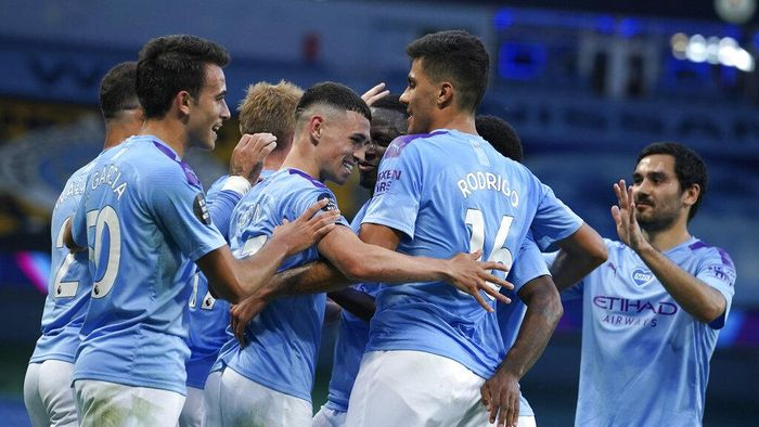 Manchester Citys Phil Foden, centre, is congratulated by teammates after scoring his teams third goal during the English Premier League soccer match between Manchester City and Liverpool at Etihad Stadium in Manchester, England, Thursday, July 2, 2020. (AP Photo/Dave Thompson,Pool)