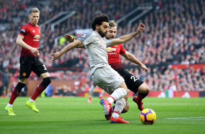 MANCHESTER, ENGLAND - FEBRUARY 24:  Mohamed Salah of Liverpool crosses the ball under pressure from Luke Shaw of Manchester United during the Premier League match between Manchester United and Liverpool FC at Old Trafford on February 24, 2019 in Manchester, United Kingdom.  (Photo by Laurence Griffiths/Getty Images)