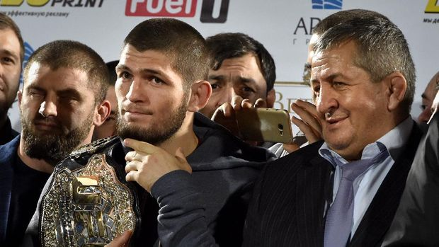 UFC lightweight champion Khabib Nurmagomedov (L) of Russia holds his champions belt next to his father Abdulmanap (C) during a ceremony upon the arrival at the Anzhi-arena stadium in Makhachkala on October 8, 2018. - He defeated Conor McGregor of Ireland in their UFC lightweight championship bout by way of submission during the UFC 229 event inside T-Mobile Arena on October 6, 2018 in Las Vegas, Nevada. (Photo by Vasily MAXIMOV / AFP)