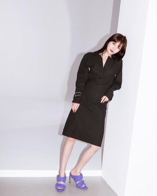 Joy mengenakan outfit yang simple dengan dress warna hitam dan curve sandals berwarna ungu.