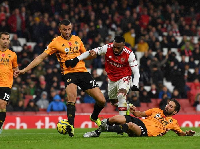 LONDON, ENGLAND - NOVEMBER 02: Alexandre Lacazette of Arsenal is tackled by Joao Moutinho of Wolverhampton Wanderers and Romain Saiss of Wolverhampton Wanderers during the Premier League match between Arsenal FC and Wolverhampton Wanderers at Emirates Stadium on November 02, 2019 in London, United Kingdom.  (Photo by Justin Setterfield/Getty Images)