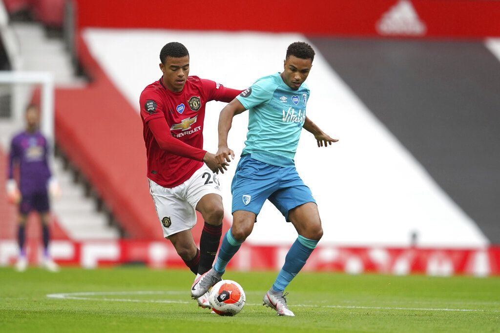 Manchester United's Mason Greenwood, left, and Bournemouth's Junior Stanislas compete for the ball during the English Premier League soccer match between Manchester United and Bournemouth at Old Trafford stadium in Manchester, England, Saturday, July 4, 2020. (AP Photo/Dave Thompson, Pool)
