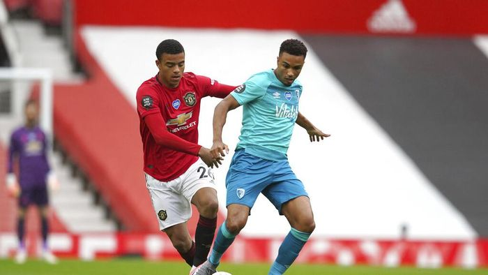 Manchester Uniteds Mason Greenwood, left, and Bournemouths Junior Stanislas compete for the ball during the English Premier League soccer match between Manchester United and Bournemouth at Old Trafford stadium in Manchester, England, Saturday, July 4, 2020. (AP Photo/Dave Thompson, Pool)