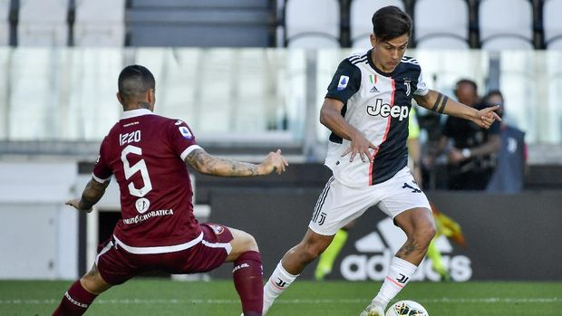 Juventus' Paulo Dybala, right, dribbles past Torino's Armando Izzo during the Serie A soccer match between Juventus and Torino, at the Allianz Stadium in Turin, Italy, Saturday, July 4, 2020. (Marco Alpozzi/LaPresse via AP)