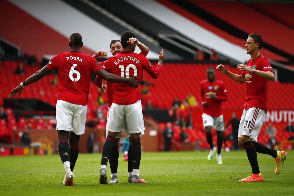 MANCHESTER, ENGLAND - JULY 04: Mason Greenwood of Manchester United celebrates with teammates Paul Pogba, Bruno Fernandes and Nemanja Matic of Manchester United after scoring his team's second goal from the penalty spot during the Premier League match between Manchester United and AFC Bournemouth  at Old Trafford on July 04, 2020 in Manchester, England. Football Stadiums around Europe remain empty due to the Coronavirus Pandemic as Government social distancing laws prohibit fans inside venues resulting in all fixtures being played behind closed doors. (Photo by Clive Brunskill/Getty Images)
