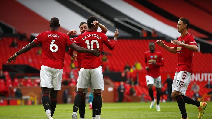 MANCHESTER, ENGLAND - JULY 04: Mason Greenwood of Manchester United celebrates with teammates Paul Pogba, Bruno Fernandes and Nemanja Matic of Manchester United after scoring his teams second goal from the penalty spot during the Premier League match between Manchester United and AFC Bournemouth  at Old Trafford on July 04, 2020 in Manchester, England. Football Stadiums around Europe remain empty due to the Coronavirus Pandemic as Government social distancing laws prohibit fans inside venues resulting in all fixtures being played behind closed doors. (Photo by Clive Brunskill/Getty Images)