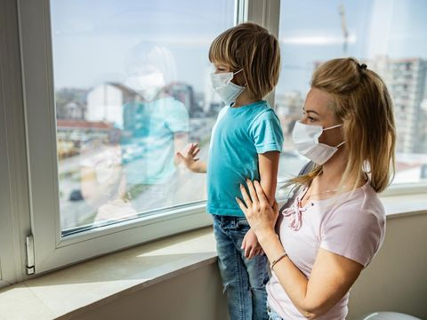 Single mother and her small son with face masks looking through window while being in isolation at home. Focus is on boy.