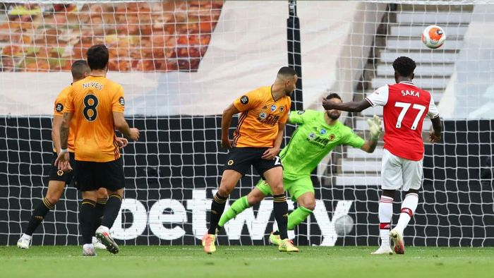 WOLVERHAMPTON, ENGLAND - JULY 04: Bukayo Saka of Arsenal scores his teams first goal during the Premier League match between Wolverhampton Wanderers and Arsenal FC at Molineux on July 04, 2020 in Wolverhampton, England. Football Stadiums around Europe remain empty due to the Coronavirus Pandemic as Government social distancing laws prohibit fans inside venues resulting in all fixtures being played behind closed doors. (Photo by Michael Steele/Getty Images)