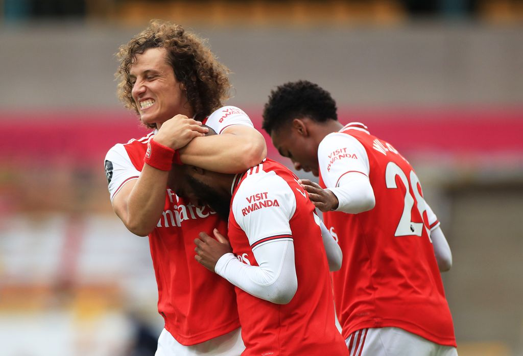 WOLVERHAMPTON, ENGLAND - JULY 04: Alexandre Lacazette of Arsenal celebrates with teammate David Luiz after scoring his team's second goal during the Premier League match between Wolverhampton Wanderers and Arsenal FC at Molineux on July 04, 2020 in Wolverhampton, England. Football Stadiums around Europe remain empty due to the Coronavirus Pandemic as Government social distancing laws prohibit fans inside venues resulting in all fixtures being played behind closed doors. (Photo by Mike Egerton/Pool via Getty Images)