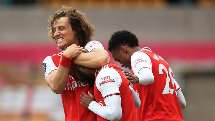 WOLVERHAMPTON, ENGLAND - JULY 04: Alexandre Lacazette of Arsenal celebrates with teammate David Luiz after scoring his teams second goal during the Premier League match between Wolverhampton Wanderers and Arsenal FC at Molineux on July 04, 2020 in Wolverhampton, England. Football Stadiums around Europe remain empty due to the Coronavirus Pandemic as Government social distancing laws prohibit fans inside venues resulting in all fixtures being played behind closed doors. (Photo by Mike Egerton/Pool via Getty Images)