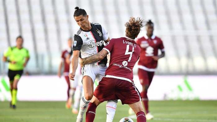 TURIN, ITALY - JULY 04:  Cristiano Ronaldo (L) of Juventus is tackled by Vojnovic Lyanco of Torino FC during the Serie A match between Juventus and Torino FC at Allianz Stadium on July 4, 2020 in Turin, Italy.  (Photo by Valerio Pennicino/Getty Images )
