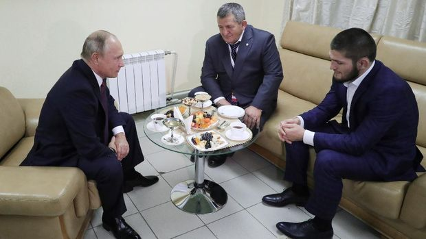 Russian President Vladimir Putin (L) speaks with UFC lightweight champion Khabib Nurmagomedov (R) and his father Abdulmanap (C) during their meeting at the Russia is a Sport State forum in Ulyanovsk on October 10, 2018. - Unbeaten Khabib Nurmagomedov will not be stripped of his UFC lightweight title despite his role in a post-match brawl Saturday, UFC president Dana White said in a website posting October 10, 2018. (Photo by Mikhail KLIMENTYEV / SPUTNIK / AFP)
